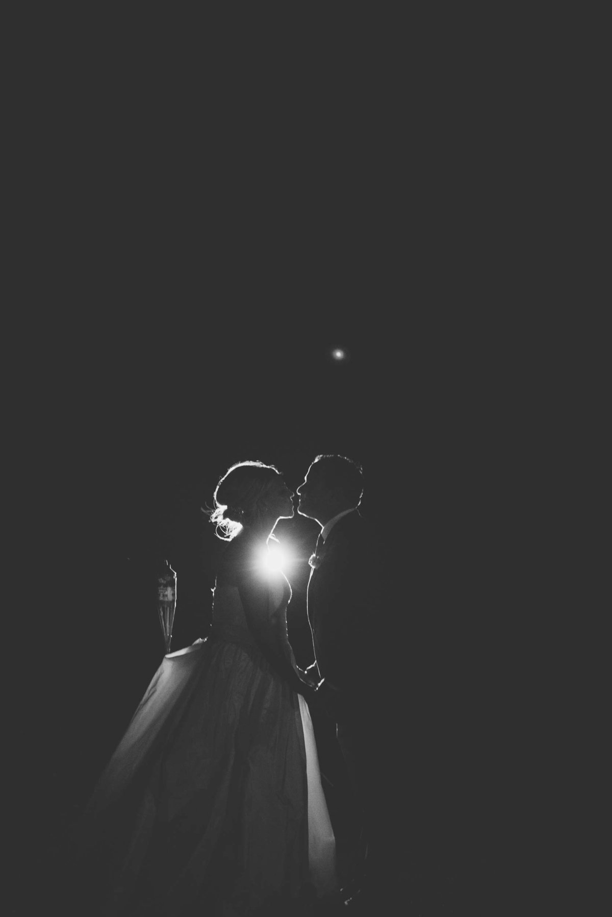 Bride and groom kissing with light shining from behind at Huntington Crescent Club
