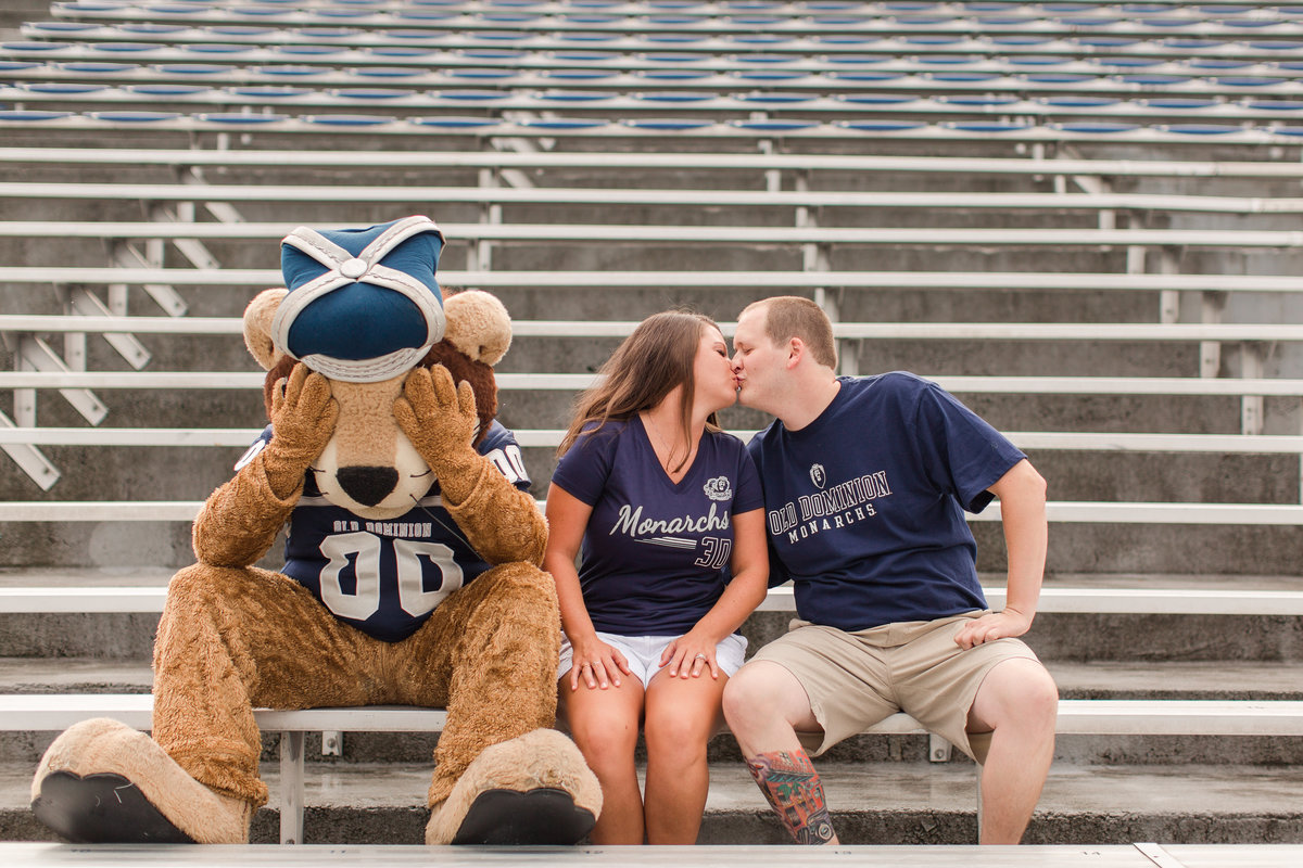 ODU's Big Blue covering his eyes while couple kiss on the bleachers