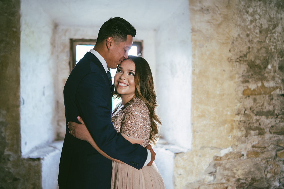Engaged couple holding each other inside Mission San Jose in San Antonio