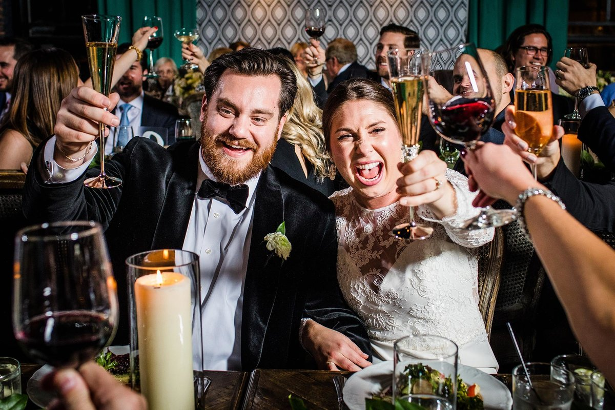 A bride and groom cheer their guests at a Boarding House Chicago wedding.