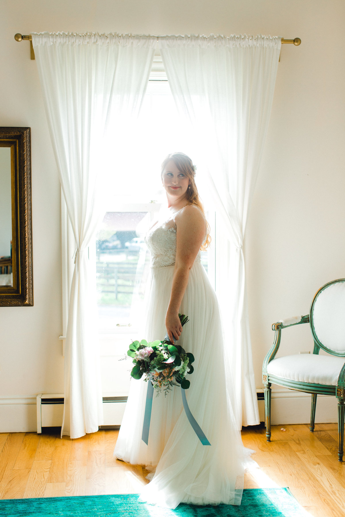 Bride posing in dress with bouquet in bridal suite at Olympias Valley Estate in Petaluma California