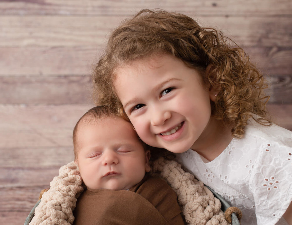Newborn boy and big sister posed cheek to cheek in our Rochester, NY studio.