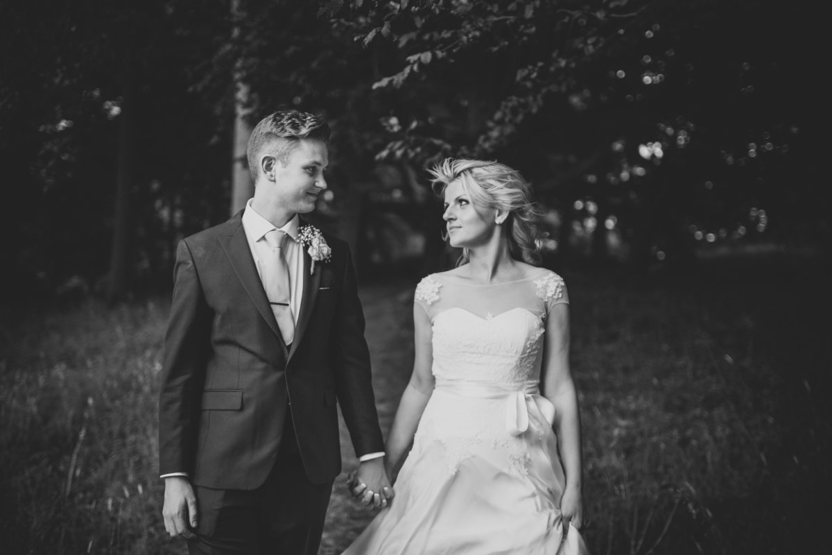 b&w photograph of the bride and groom walking through the woods at comberemere abbey