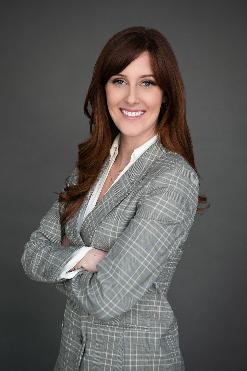 Business headshot of woman crossing her arms in blazer