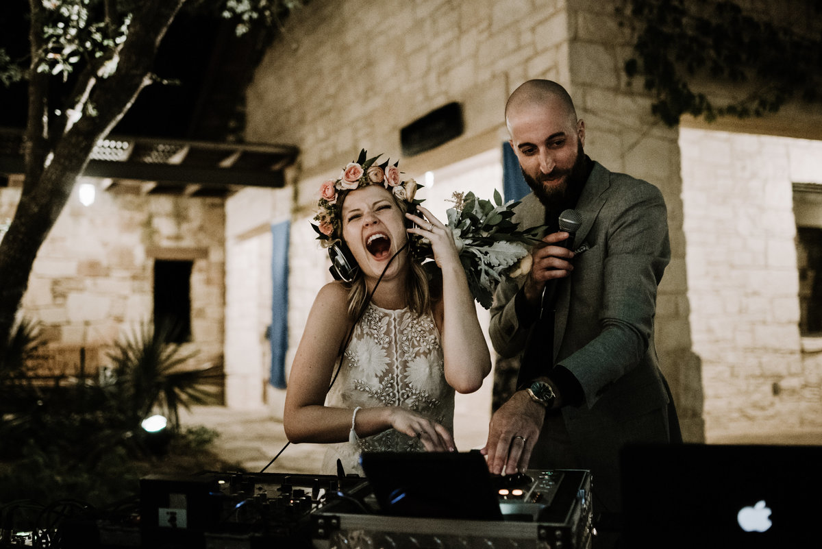 bride behind dj table wedding