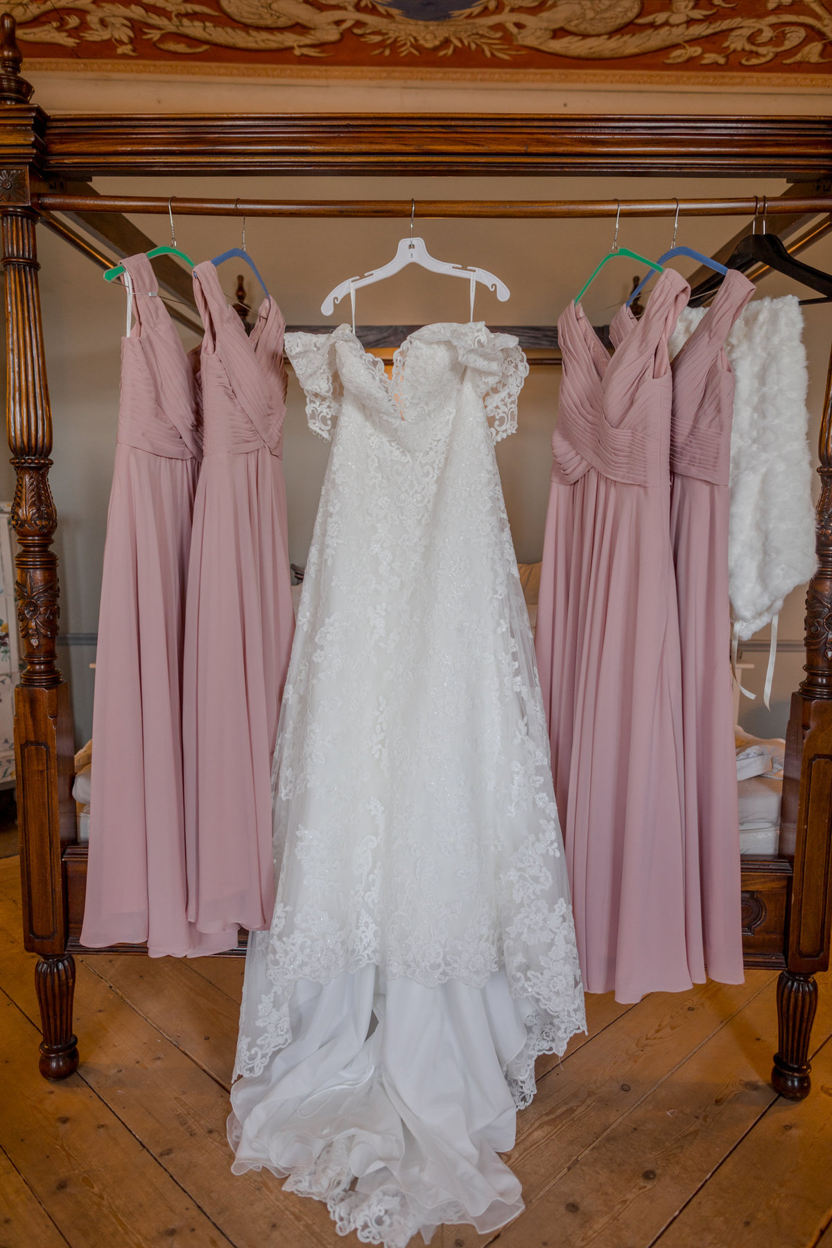 A closeup of the bridal wedding gown and the two pink bridesmaid dresses on each side