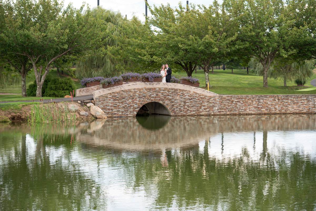 distant photo of bride and groom on bridge at golf course at Willow Creek Golf and Country Club wedding