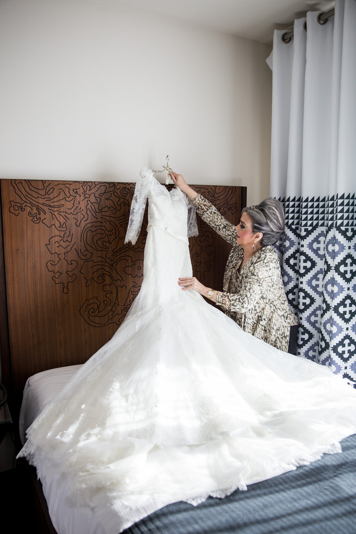 Mother of bride hangs wedding gown on bed during getting ready at Hotel Contessa in downtown San Antonio