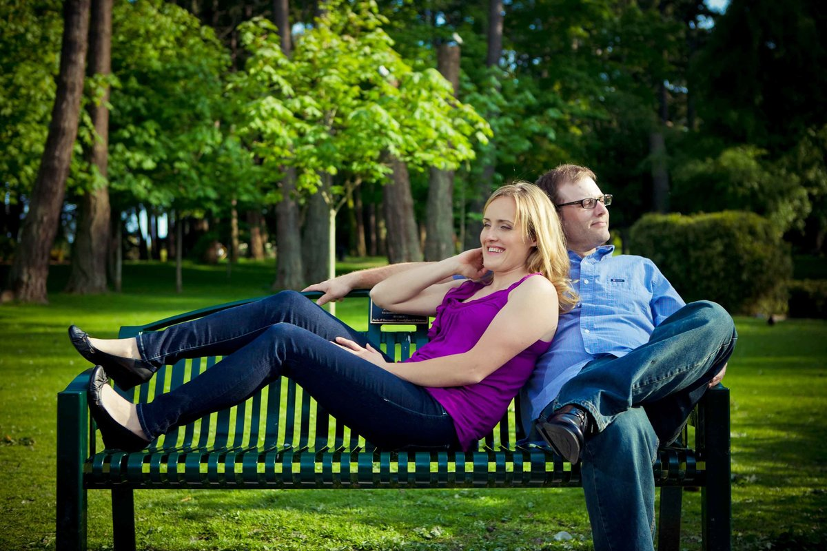 Couple relax on bench in Beacon Hill Park Victoria