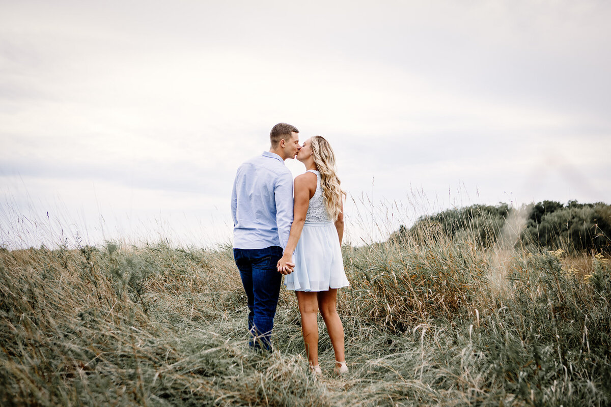 Engaged couple kissing in field in Buffalo Outer Harbour, New York