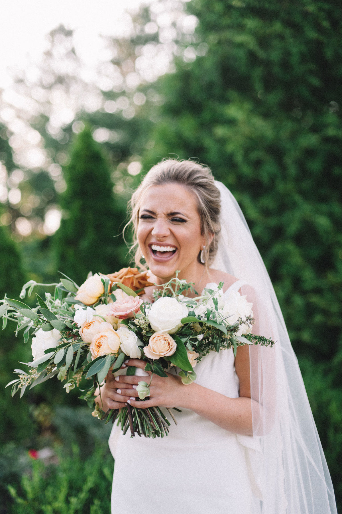 Cute bride laughing with her wedding flower bouquet at Park Crest in Hoover AL
