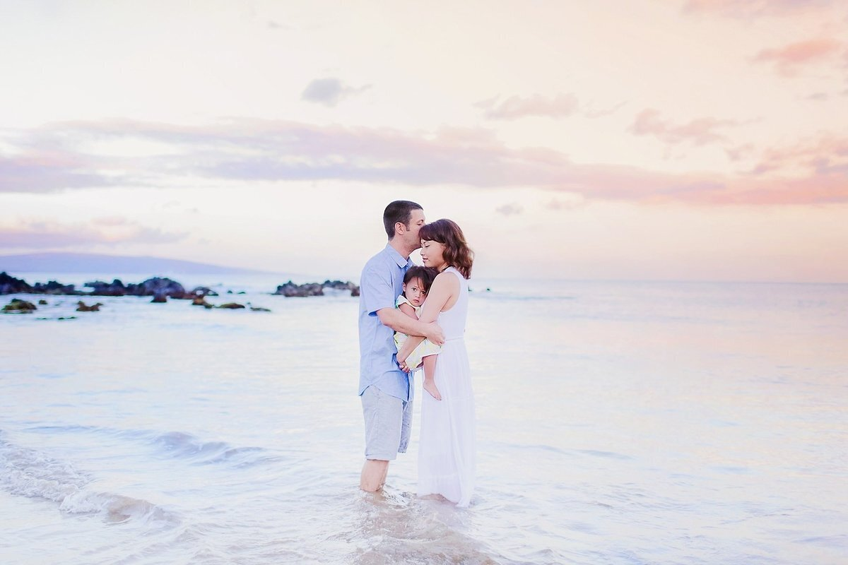 Grumpy toddler cuddles her parents during their Maui family portrait session