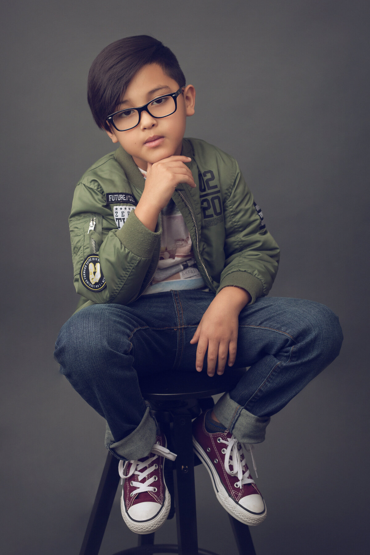 Portrait of a boy sitting on a stool, chin on his hand. Luxury Portraits.
