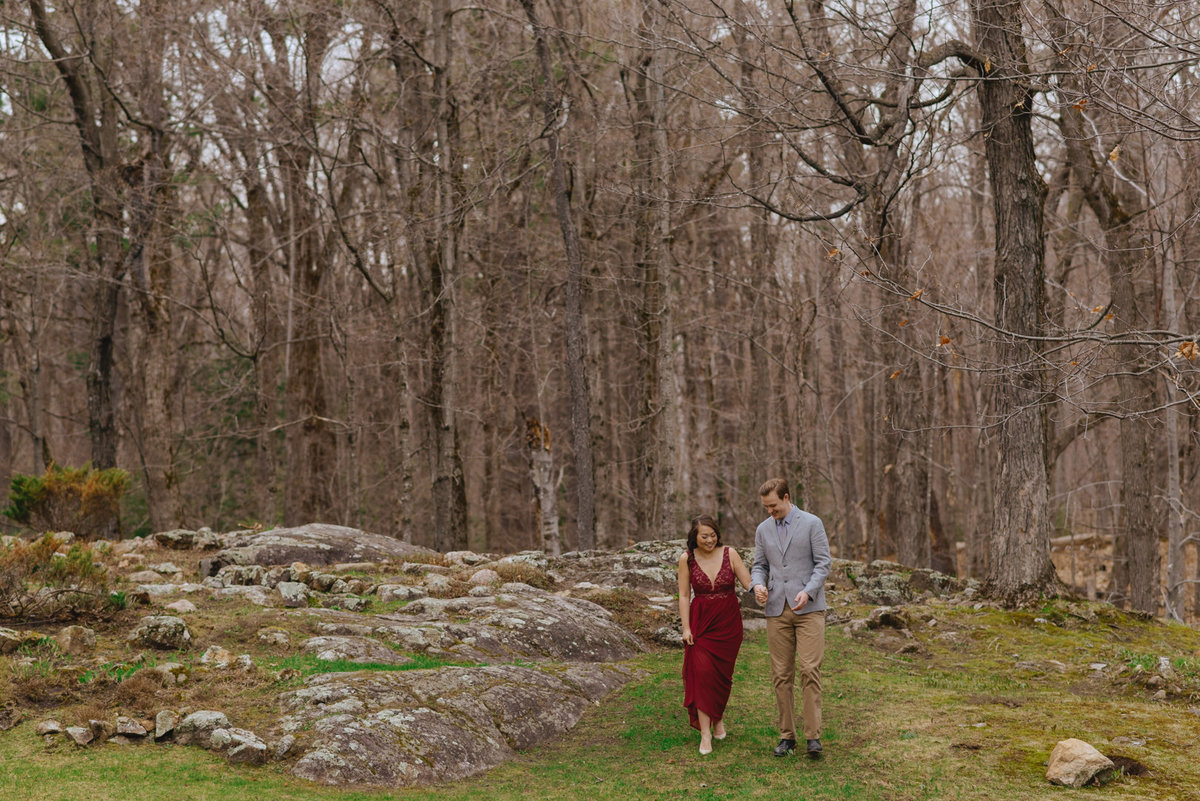 engaged couple walking through the forest