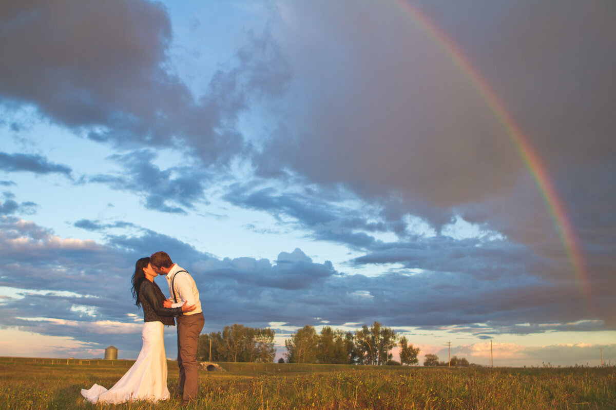 couple standing in a field with a rainbow