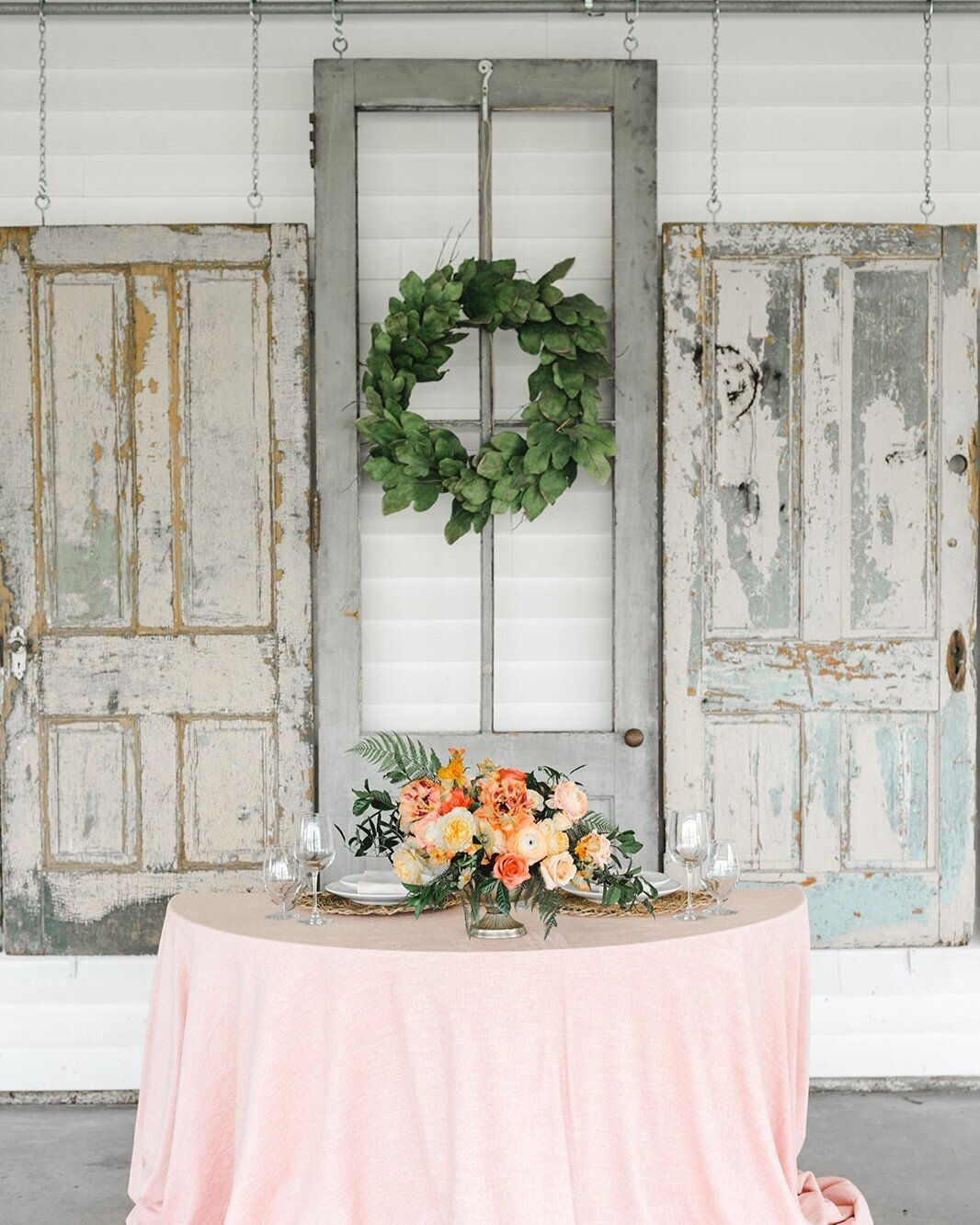 Rustic barn doors hanging in the background of a beautiful pink table scape