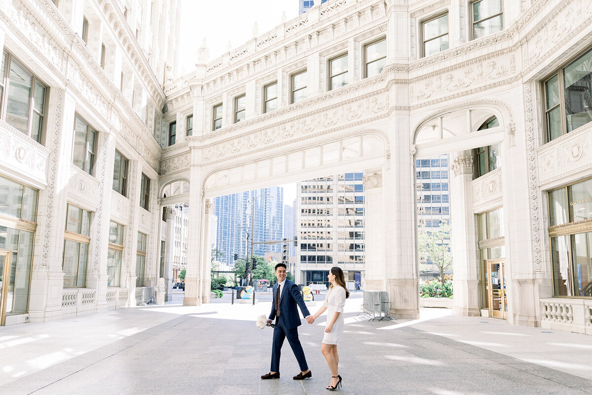 bride and groom walk near the chicago wrigley building