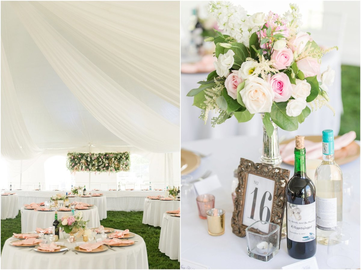 Tent reception decor, wine bottles, rose napkins, floral backdrop, pink and white flowers in vases, framed table numbers