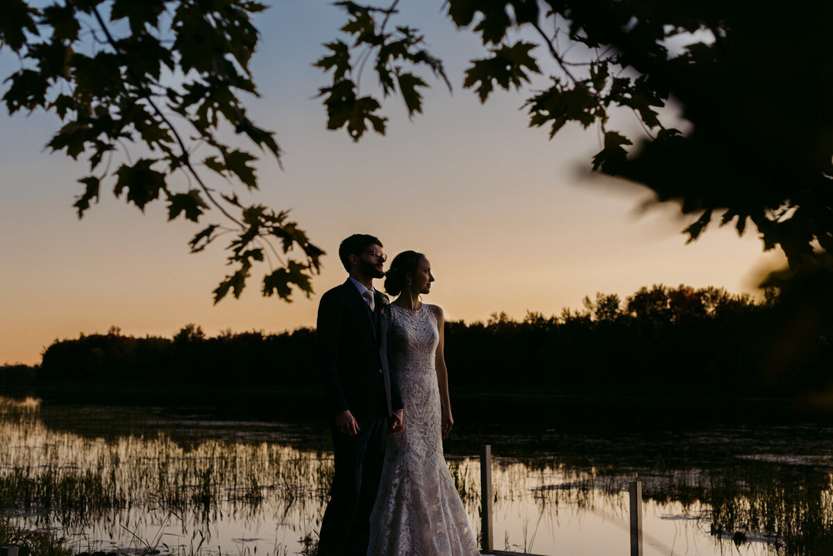 bride and groom standing on a dock at sunset