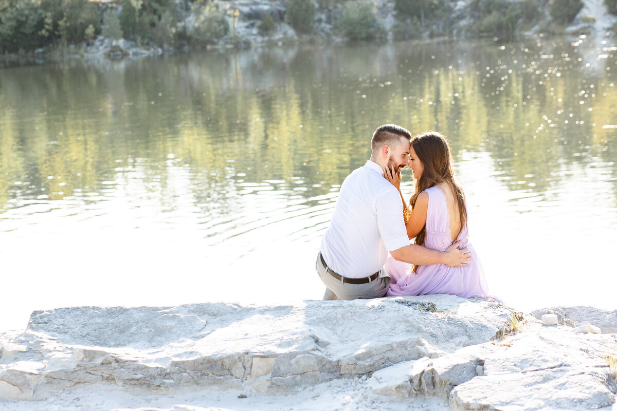 Summer Sunset Romantic Engagement Session in lavender maxi dress on rock by water at Klondike Park in St. Louis by Amy Britton Photography Photographer in St. Louis