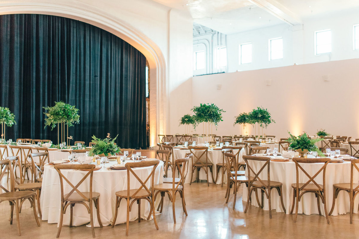 wood chairs with greenery tall centerpieces