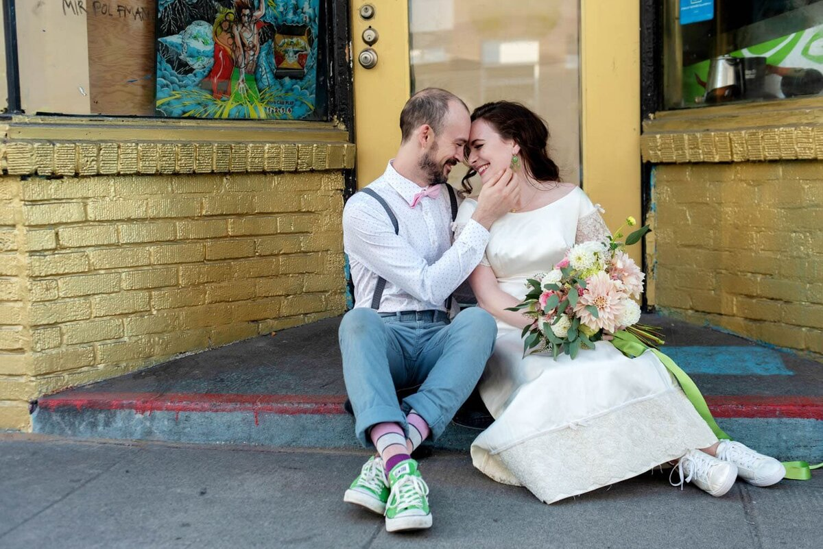 a bride in a vintage dress and a hipster groom sit on a stoop in front of a fun yellow wall in se portland