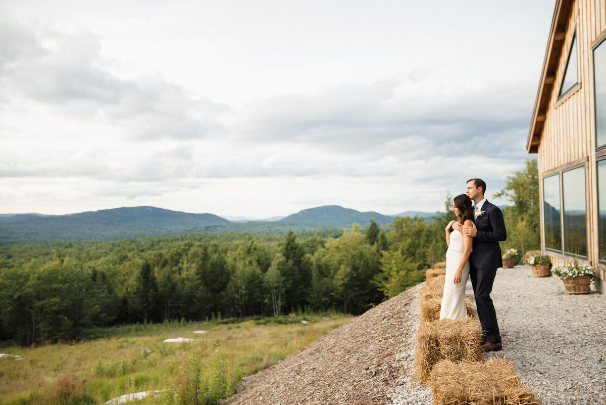 bride and groom overlooking mountain in front of barn in Maine