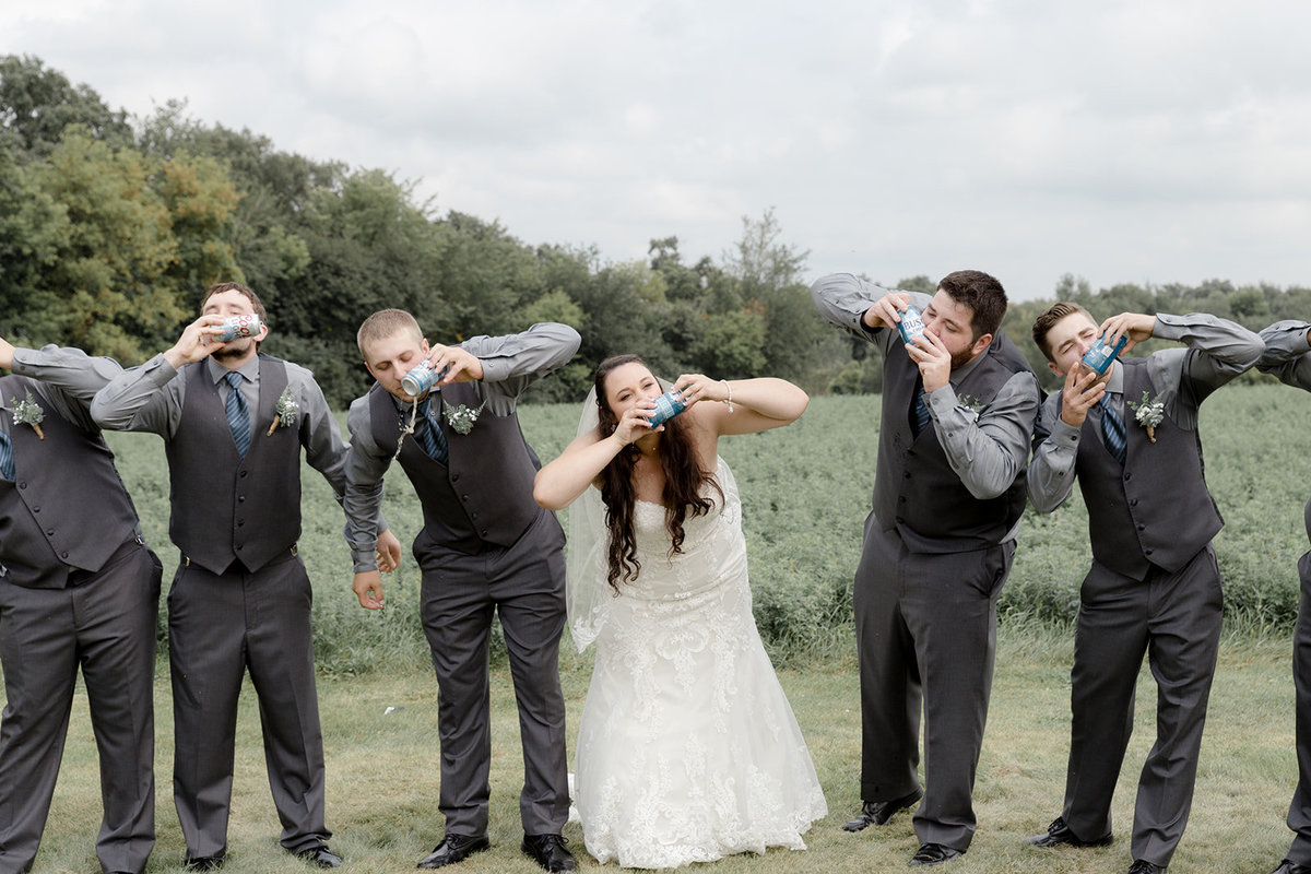 Bride and Groomsmen shotgunning a beer together in Prescott Wisconsin