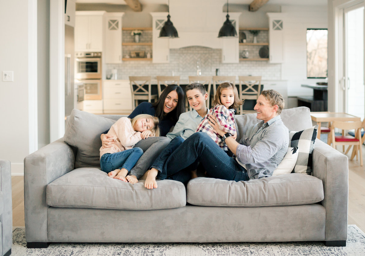 family of five cuddles on couch in new home build rochester minnesota