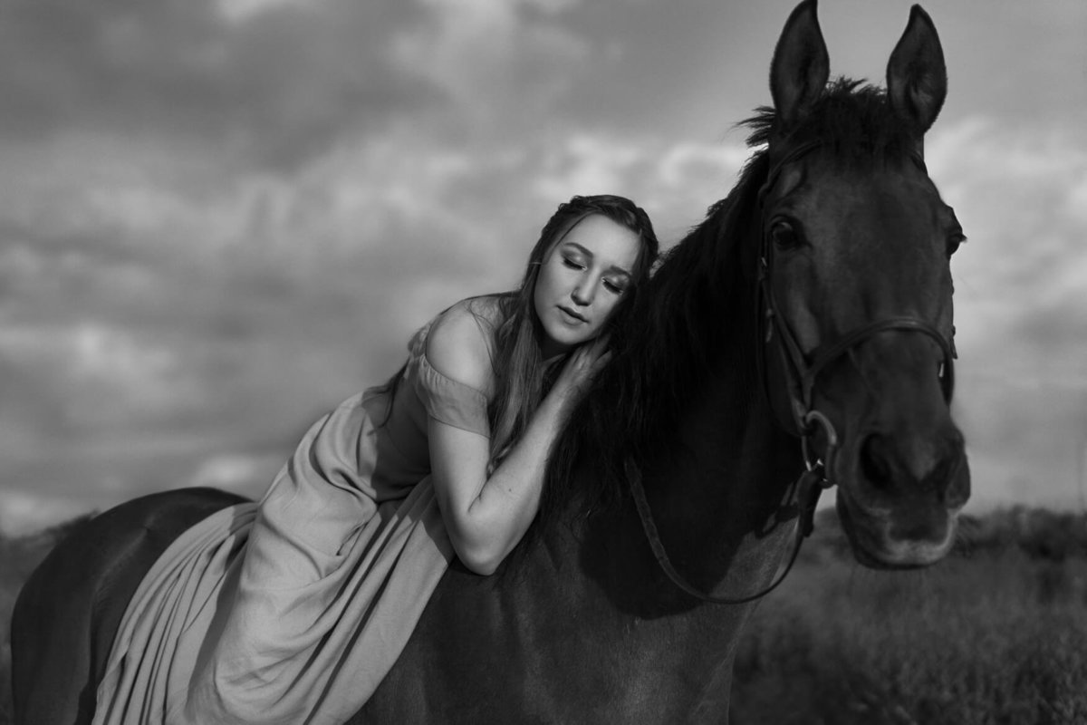 Cassidy lying on her horses back for a senior portrait shoot