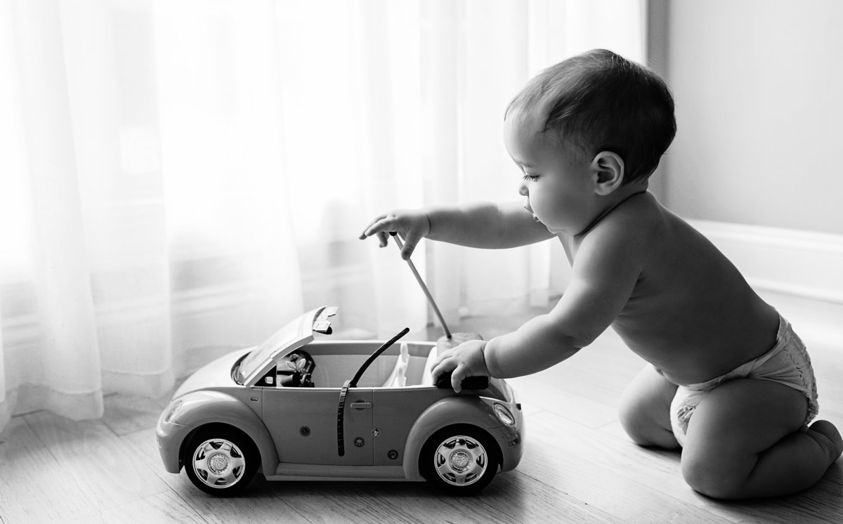 charlotte documentary photographer captures beautiful image of a toddler playing with his car next to a window