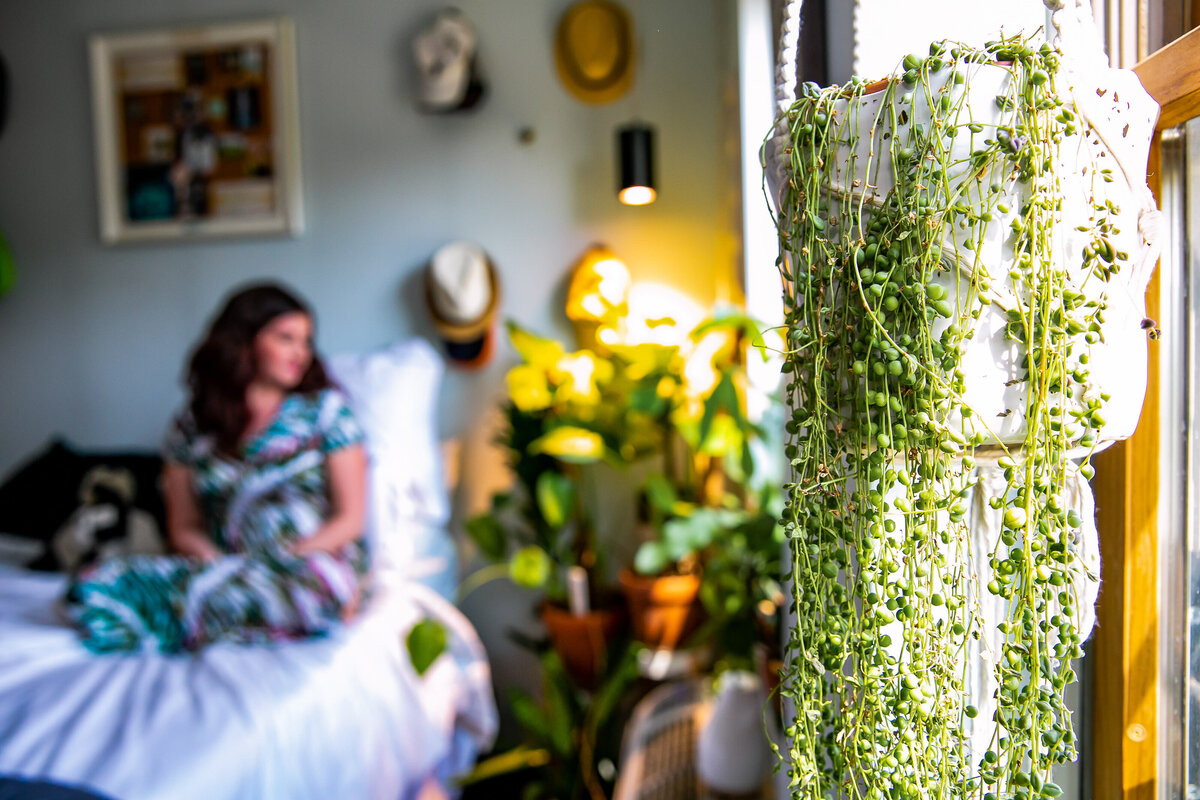 Maria, host of Bloom & Grow Radio podcast, sits on her bed admiring her indoor plant jungle