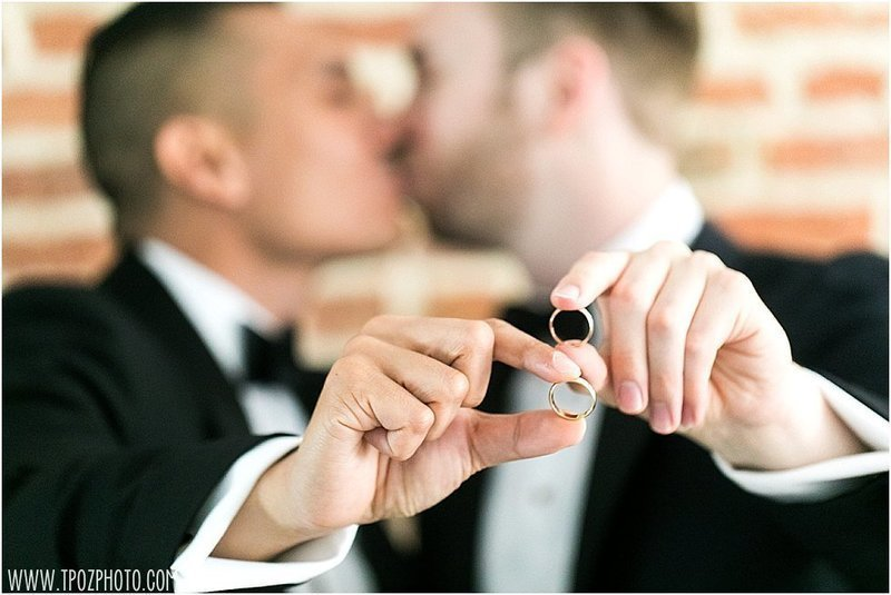 Gay couple with wedding rings kissing