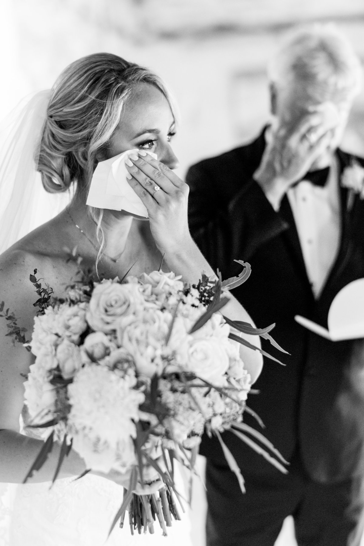 Bride wiping off tears after seeing her father on her wedding day