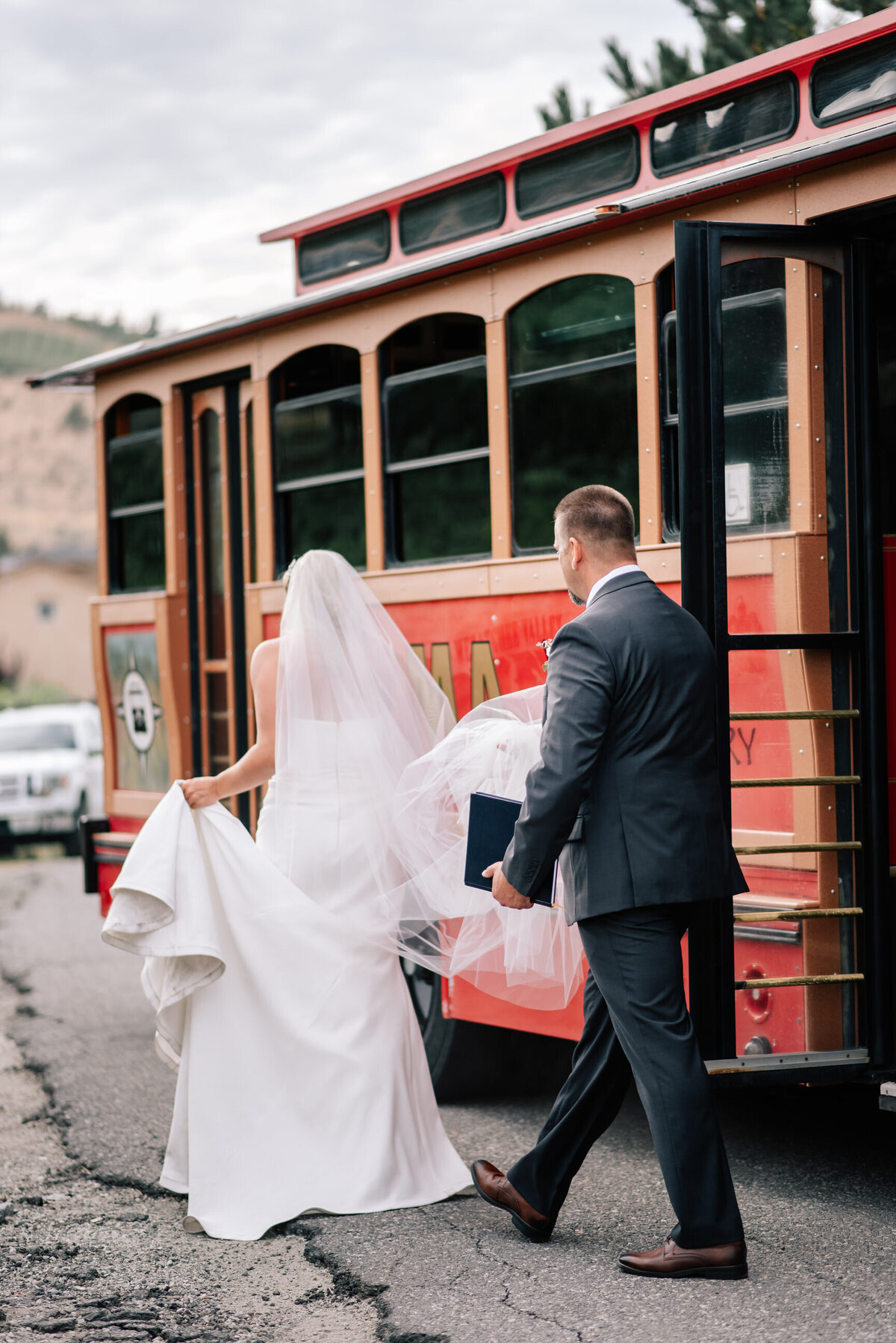 Bride and father getting off the red trolley at Karma Vineyards in Chelan, WA