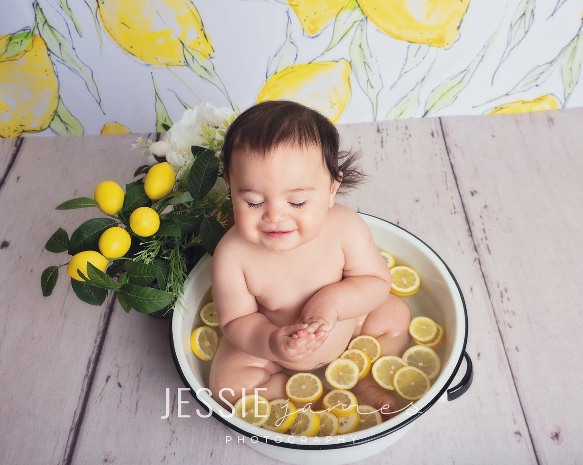 baby girl in a bath with lemons