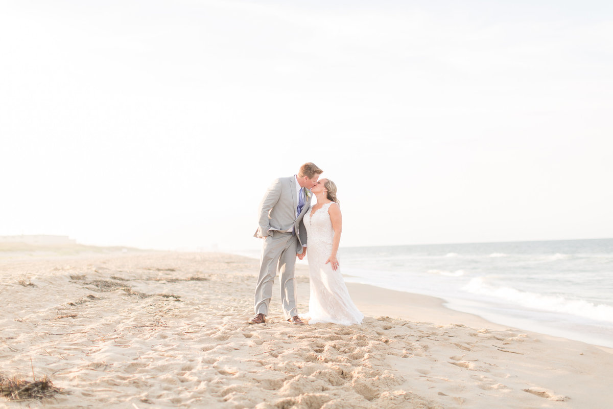 Groom kissing bride on the beach in Virginia Beach, VA
