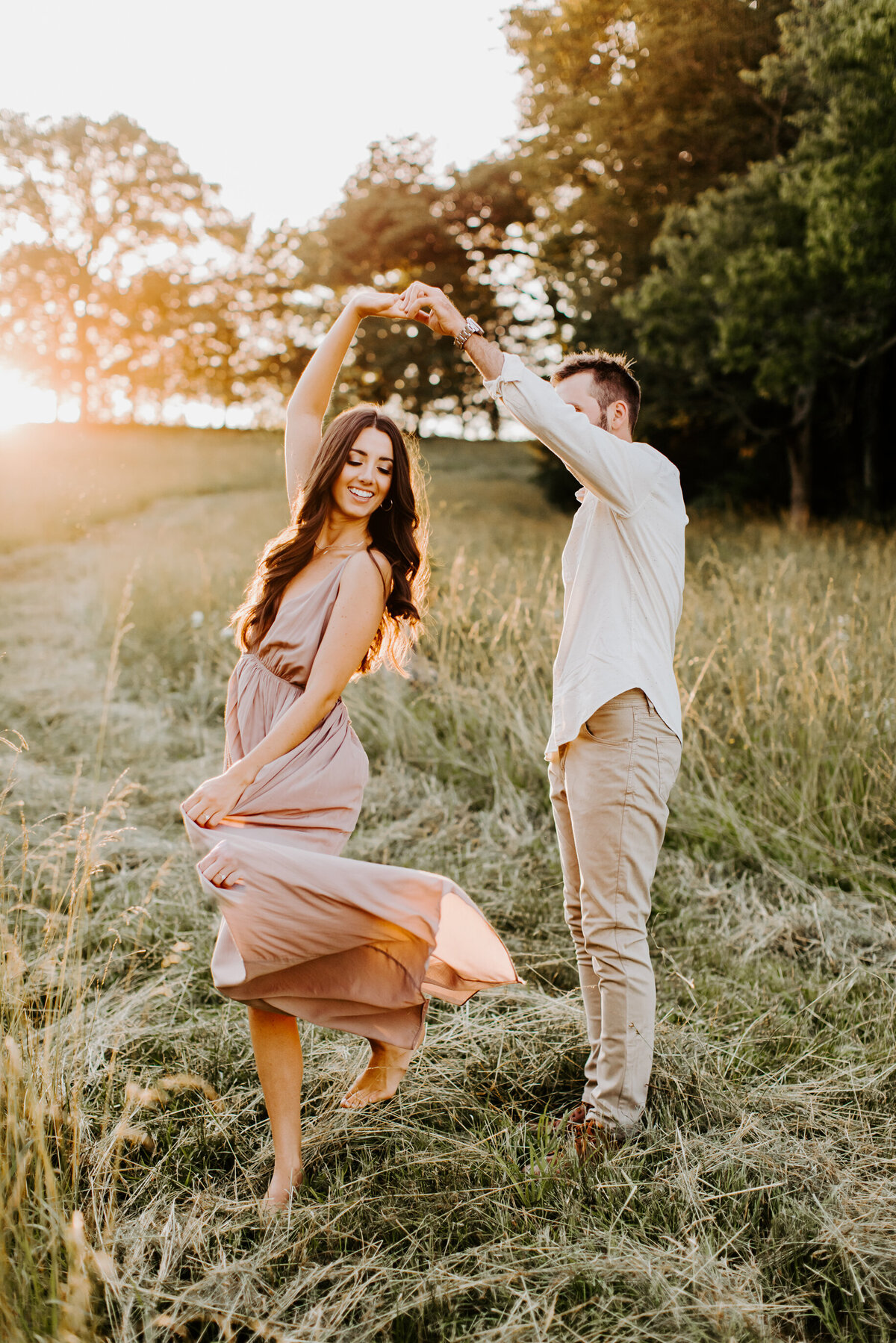 couple dancing in a field at golden hour