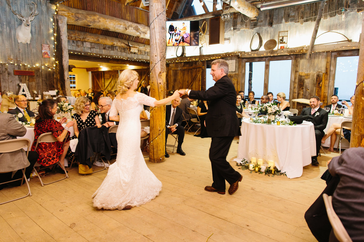 A father dances with his daughter at a wedding reception inside a barn.