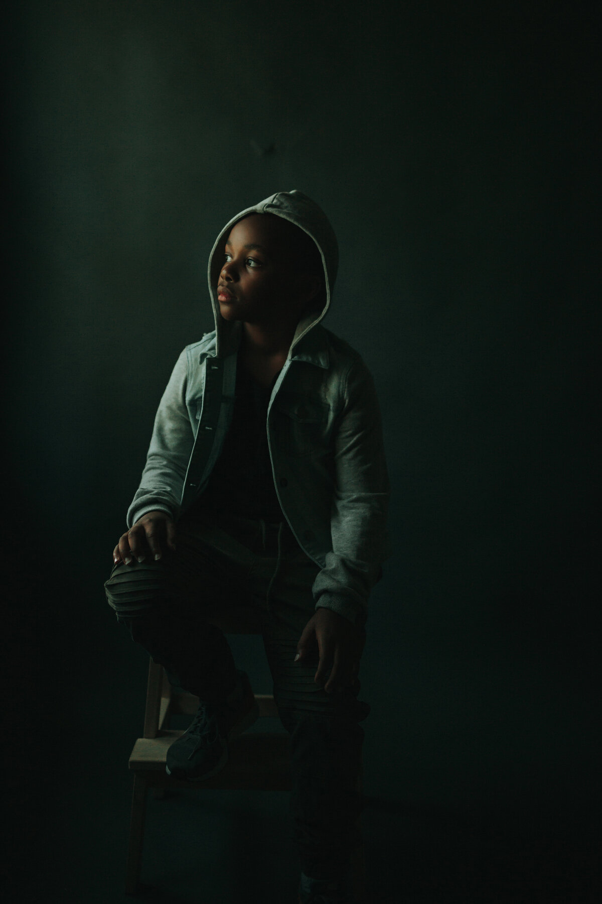 Fine art portrait of a boy in a jean hoodie and jeans, foot resting on a chair, looking camera left.