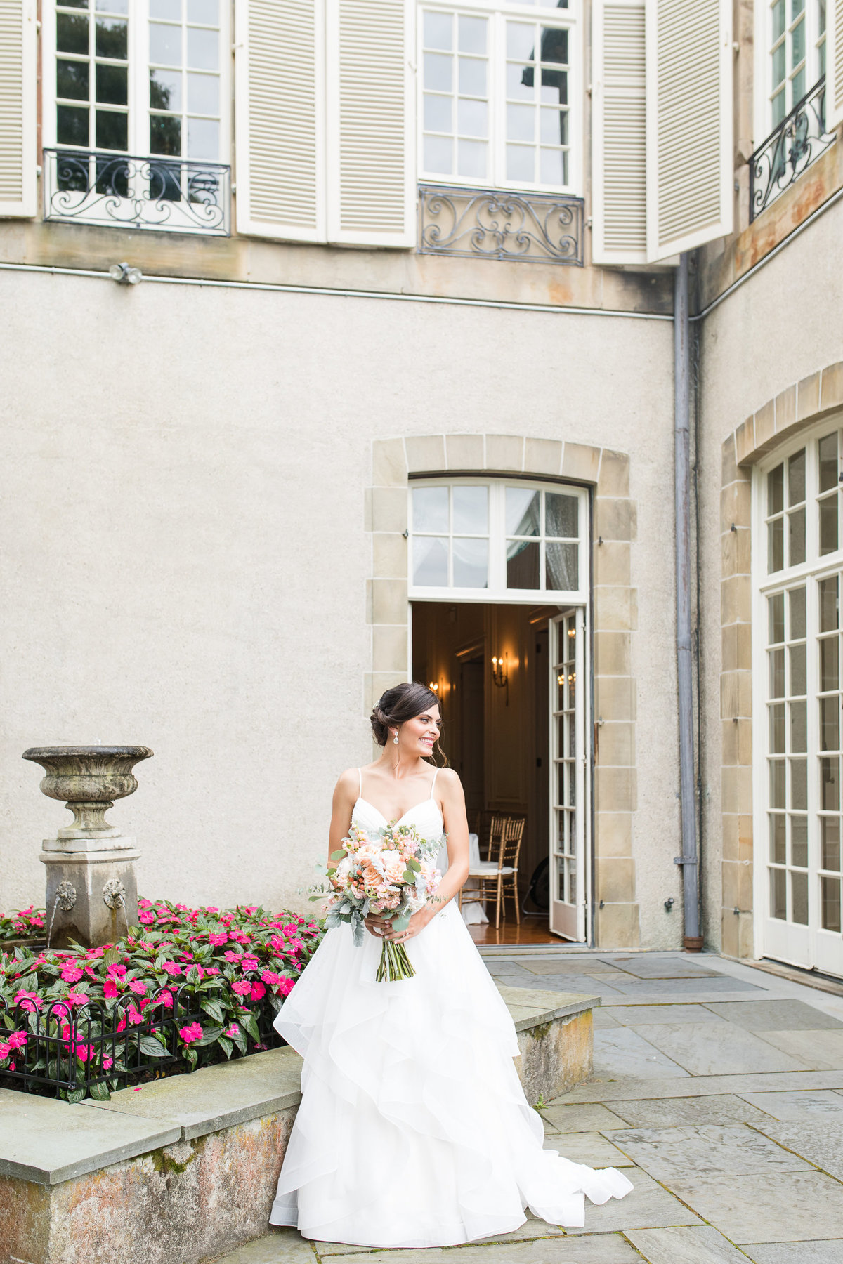 Bride stands near the fountain at Glen Manor House
