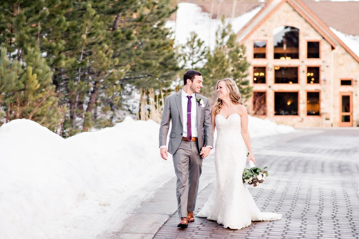 Bride and groom walking and smiling during romantic winter wedding at Della Terra Chateau in Estes Park.