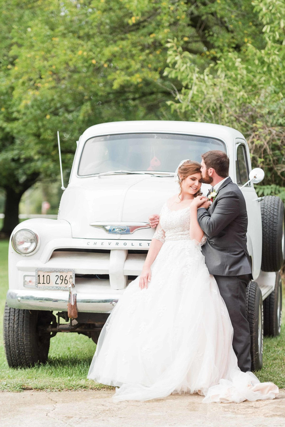 Bride and groom sharing a moment in front of vintage chevy truck.