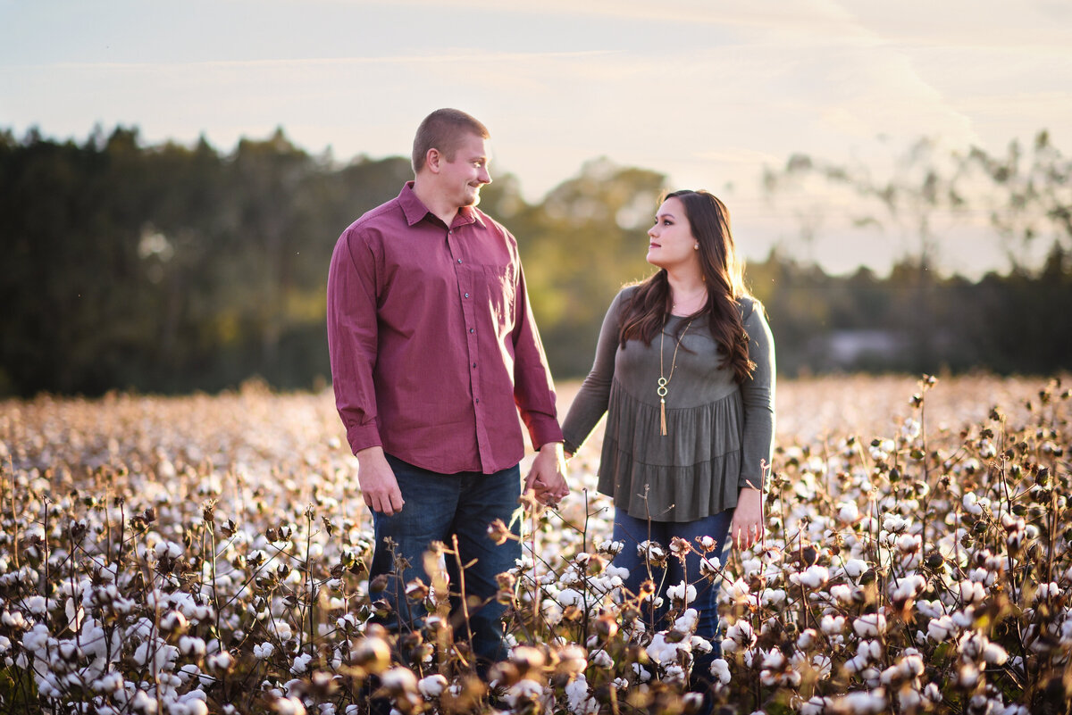Beautiful Mississippi Engagement Photography: couple holds hands and gazes at each other in Mississippi cotton field