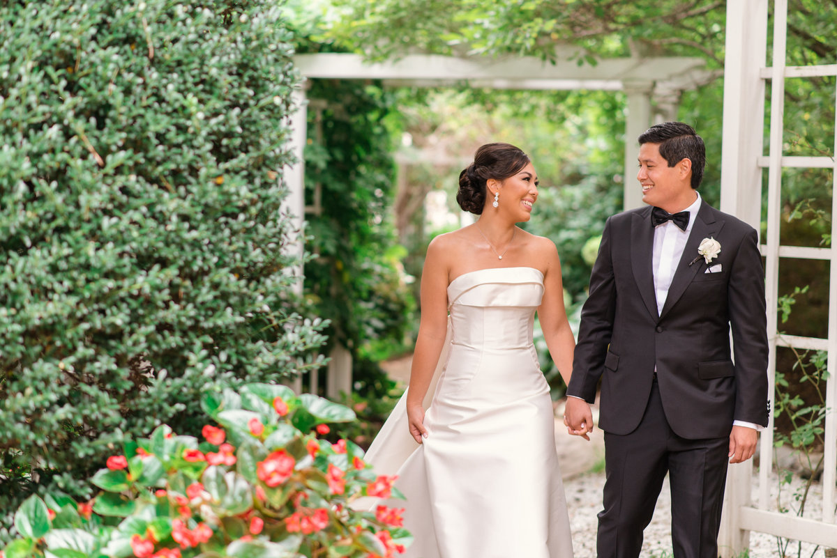 photo of bride and groom smiling and holding hands in the outdoor gardens from wedding reception at The Garden City Hotel