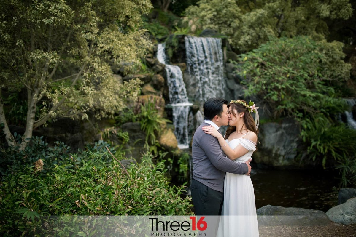 Couple shares a kiss in front of the waterfall at the LA Arboretum