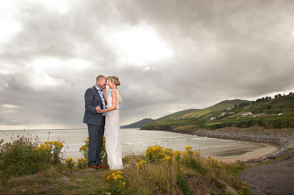blonde bride wearing a scoop -back, column style dress embracing her groom, wearing a blue suit and floral shirt standing on the edge of Inch beach, Kerry