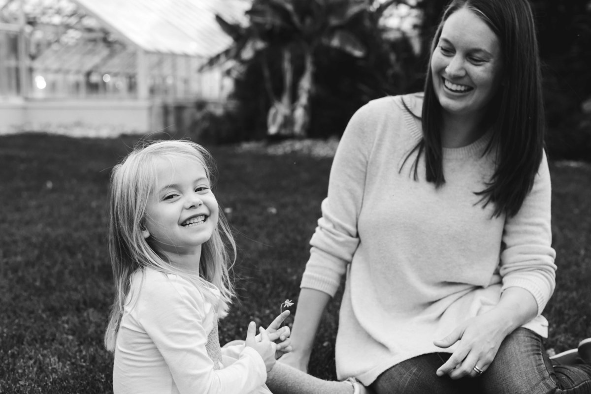 Mother and daughter sitting on the grass laughing in black and white
