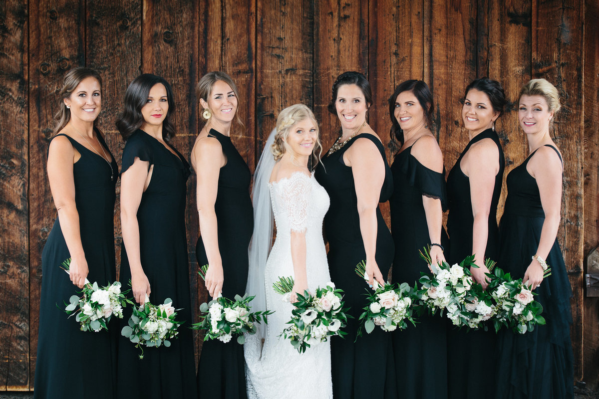A group of bridesmaids holding bouquets of flowers.