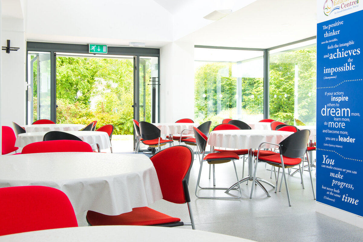 Interior photograph of canteen in office building with red chairs and white tablecloths